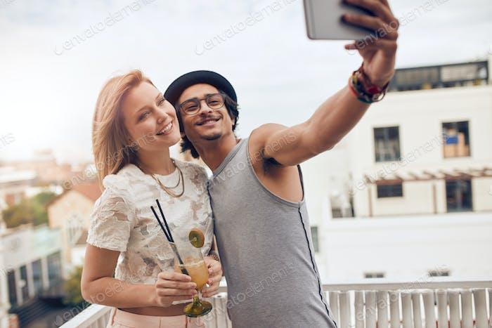 Freunde nehmen ein selfie auf ihre outdoor-dachterrasse party