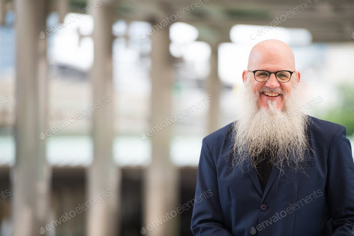 Happy mature bearded bald businessman with eyeglasses smiling in the city outdoors