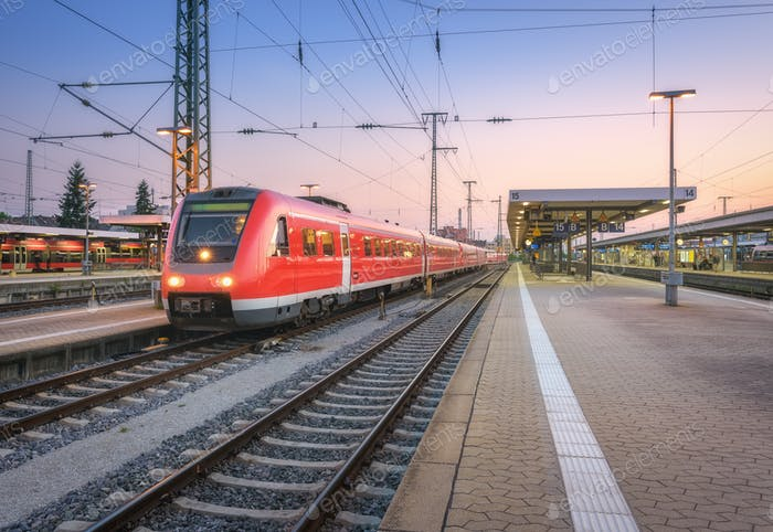 High speed red train on the railway station at dusk