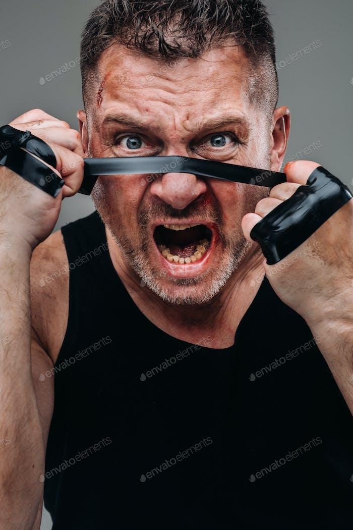 sobre un fondo gris se encuentra un hombre maltratado en una camiseta negra que parece un luchador y la preparación
