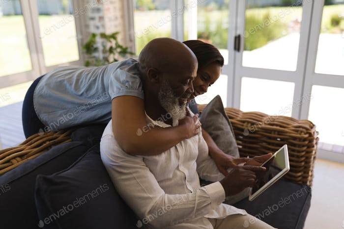 Side view of active senior couple using digital tablet in living room at home