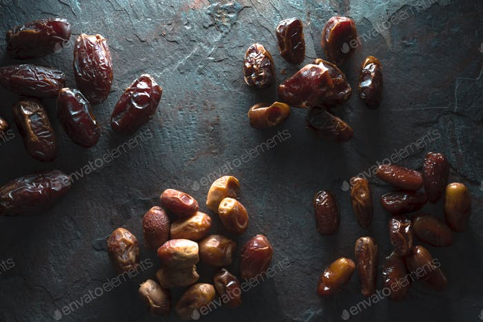 Groups of dried dates on a gray background copy space