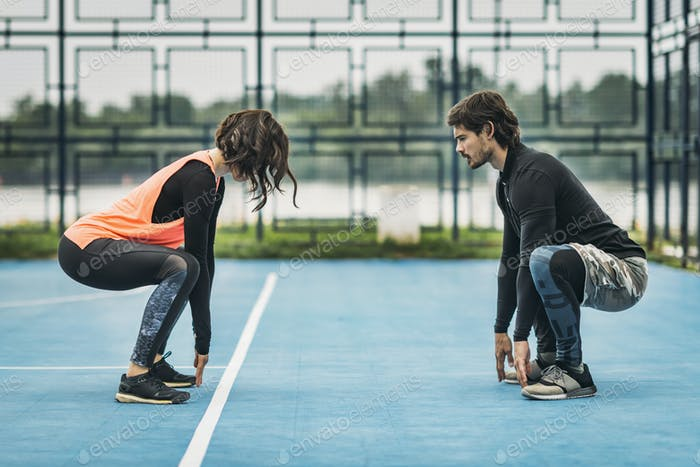 Young Female Athlete Exercising with Personal Fitness Trainer