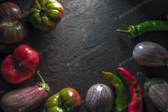 Frame of multi-colored tomatoes, aubergine and chili on a gray table free space