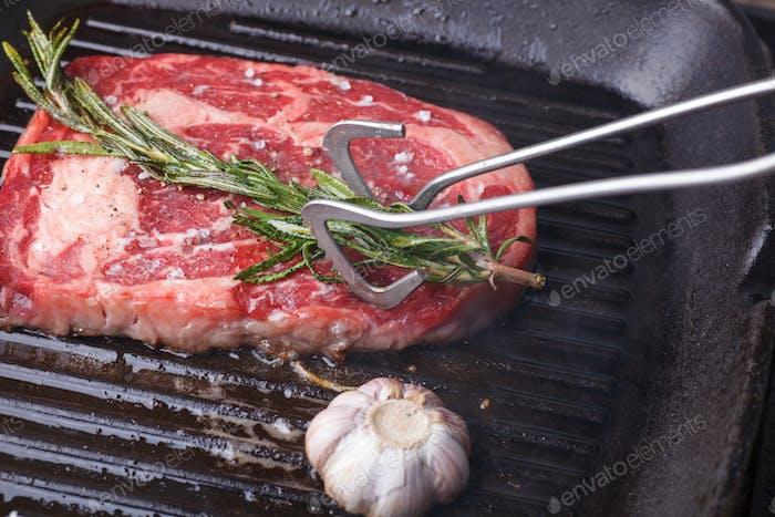 forceps greasing beef steak by rosemary
