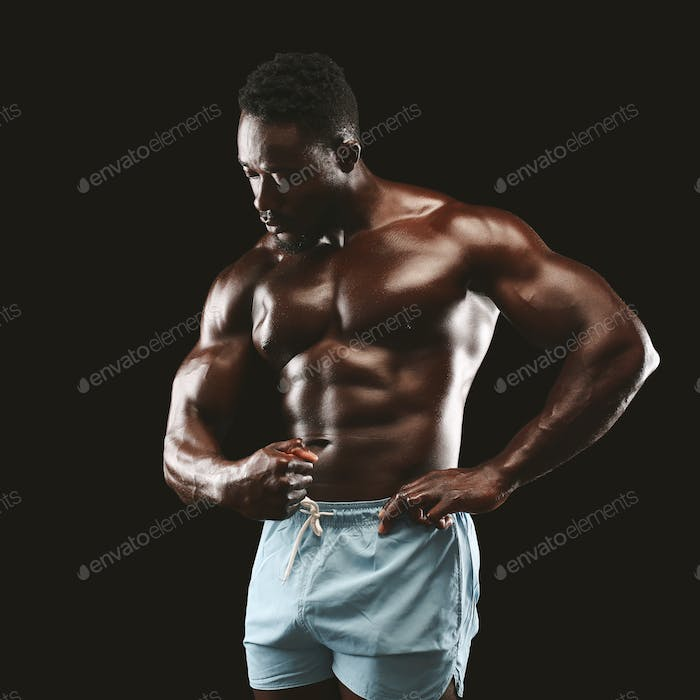 Young african fittness model displaying his abdominals