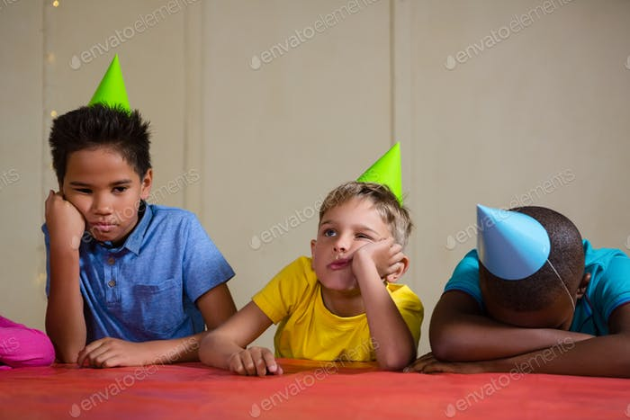 Bored children wearing party hat at table