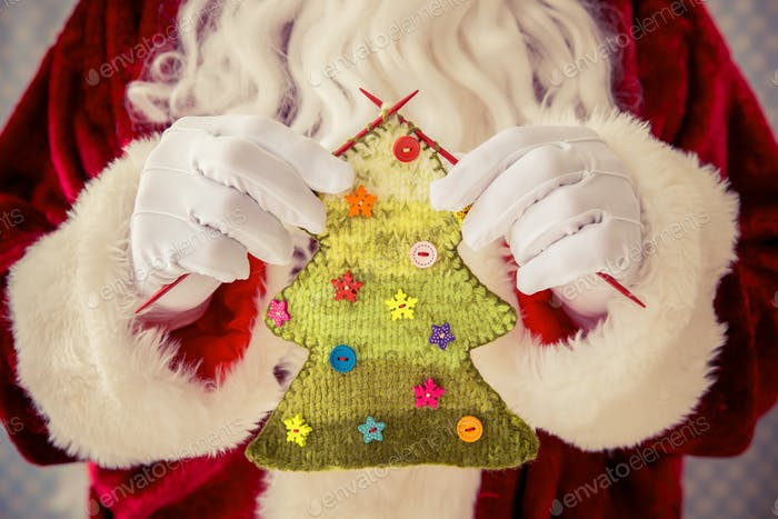 Santa Claus holding knitted Christmas tree