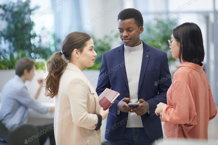 Afrikanischer Geschäftsmann im Gespräch mit Kollegen im Büro
