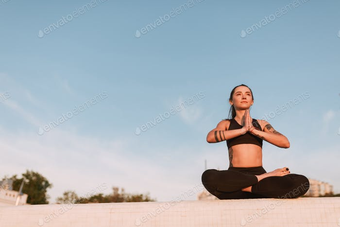 Beautiful lady sitting in lotus pose and dreamily looking aside