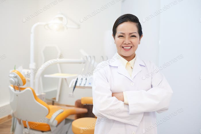 Cheerful ethnic dentist in white gown