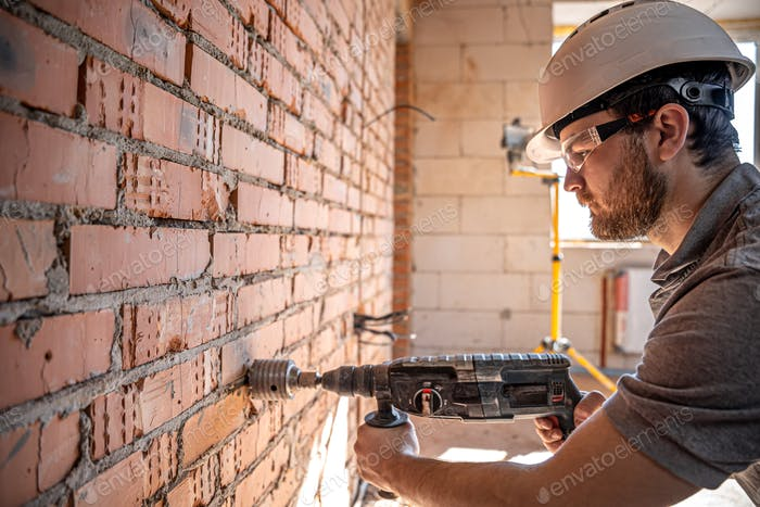 A builder in a helmet and goggles works with a drill.