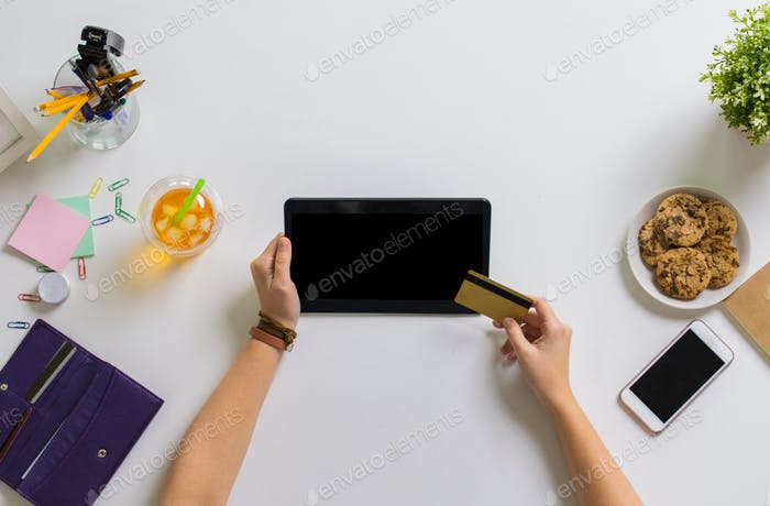 hands with tablet pc and credit card at table