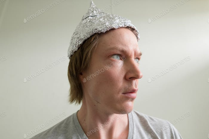 Face of young man with tin foil hat thinking inside the room