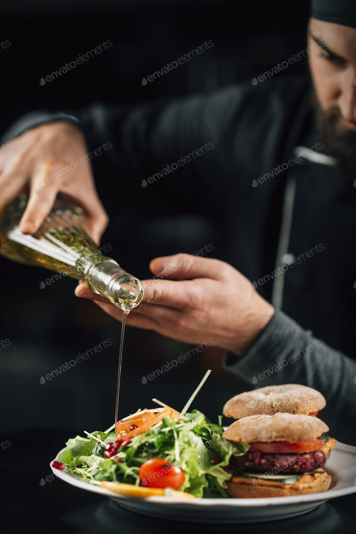 Chef Pouring Olive Oil on Salad in a Restaurant Kitchen