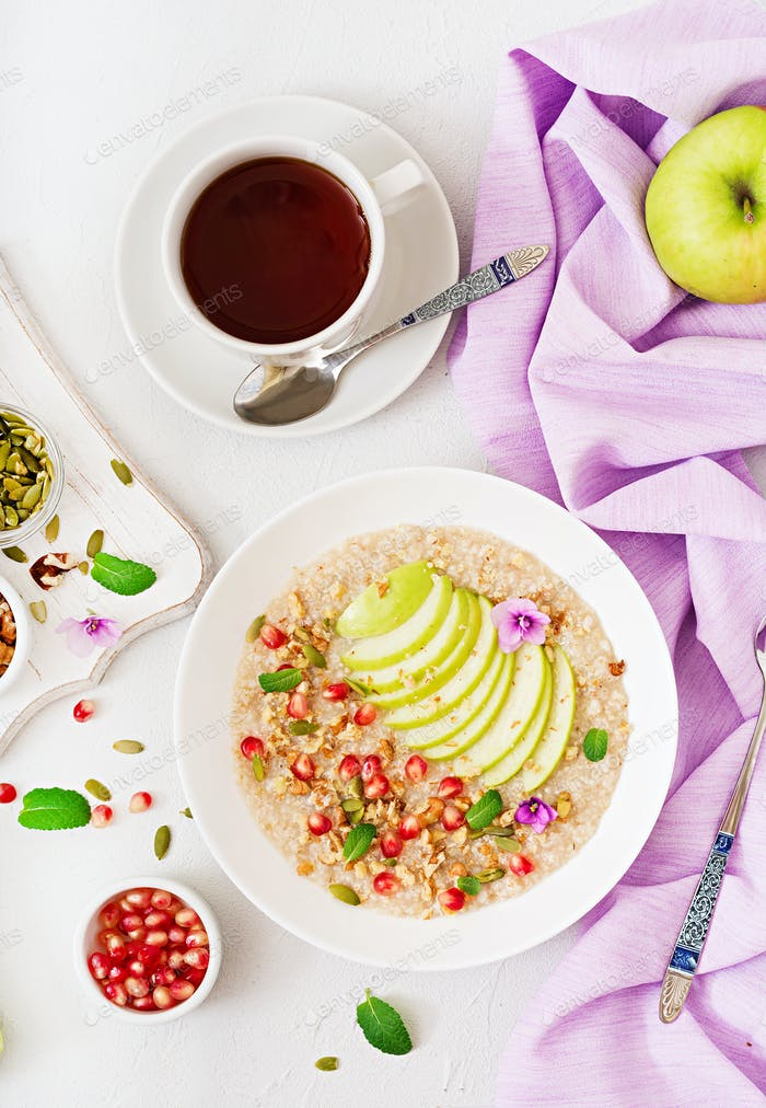Lecker und gesunder Haferbrei mit Äpfeln, Granatapfel und Nüssen