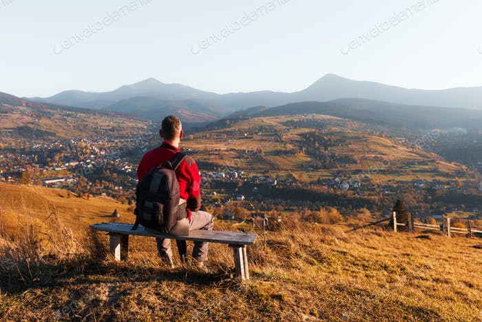 Photographer seating on wooden bench