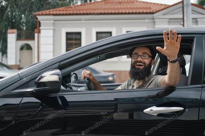 Cheerful man waving while driving a car