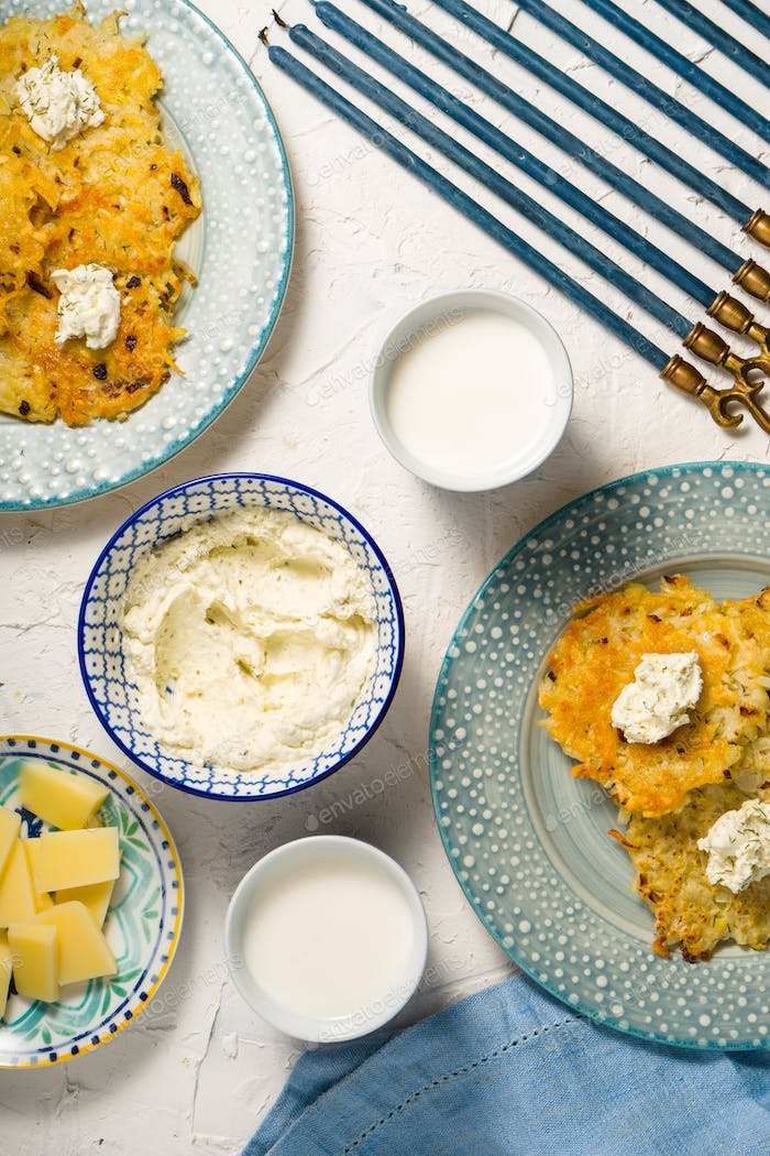 Latkes, milk and cheese cheese, Hanukkah on a white table