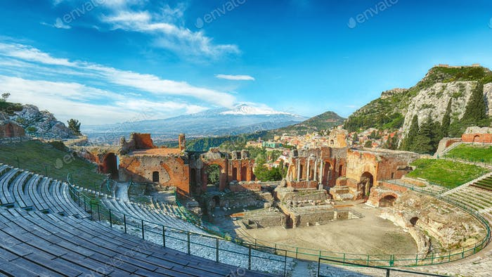 Ruins of ancient Greek theater in Taormina and Etna volcano in the background.