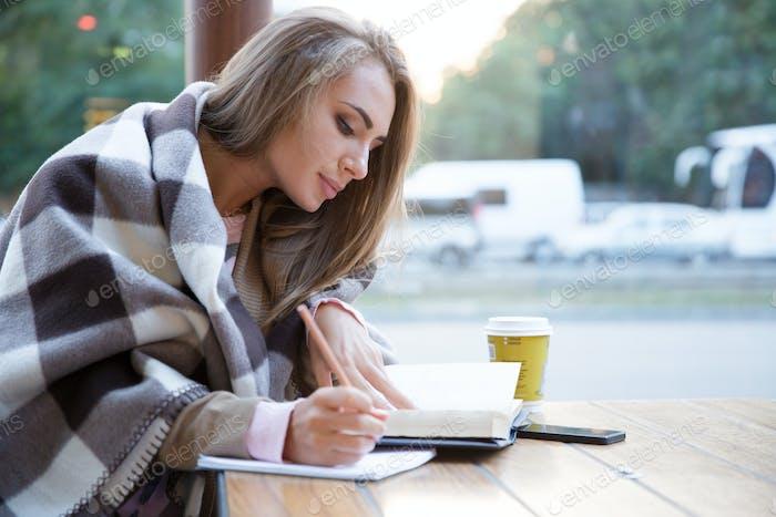Girl doing homework in cafe
