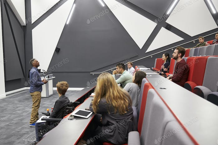 Man lectures students in lecture theatre, front row seat POV
