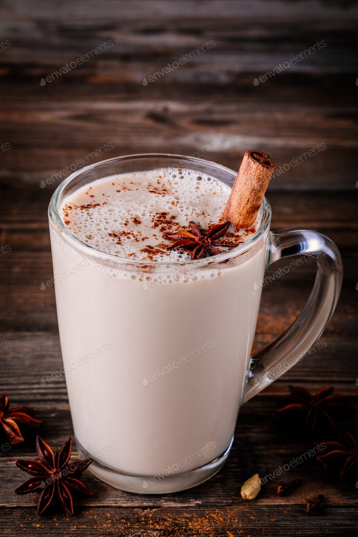 Homemade Chai Tea Latte with anise and cinnamon stick in glass mug