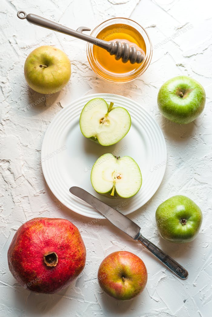 Fruits and honey on a white table for the Rosh Hashanah
