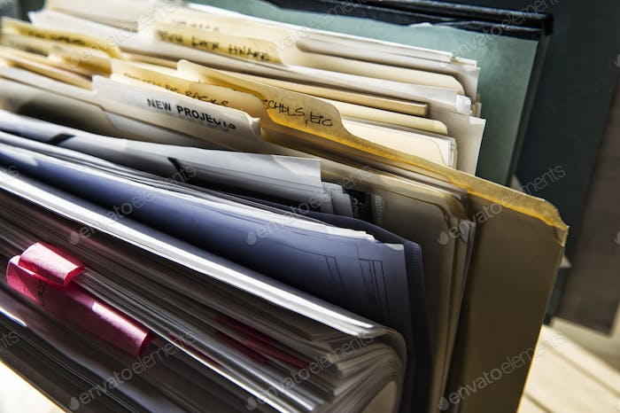 Close-up of files and file folders on a desk top in an office.