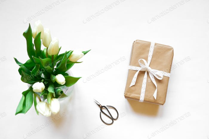 Top view of white tulips, box  gift and scissors
