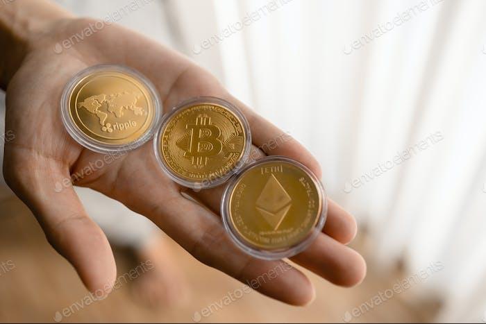 Joven sosteniendo fichas criptográficas Bitcoin, Ethereum, Ripple en la palma de la mano