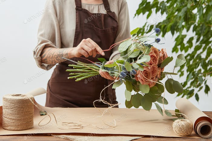 Female florist is decorating beautiful bouquet from fresh natural roses step by step at the table