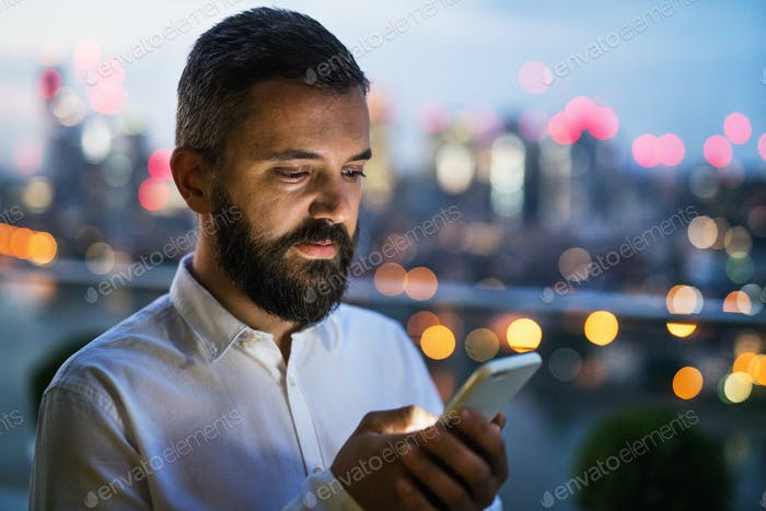 A businessman with smartphone at sunset, text messaging.