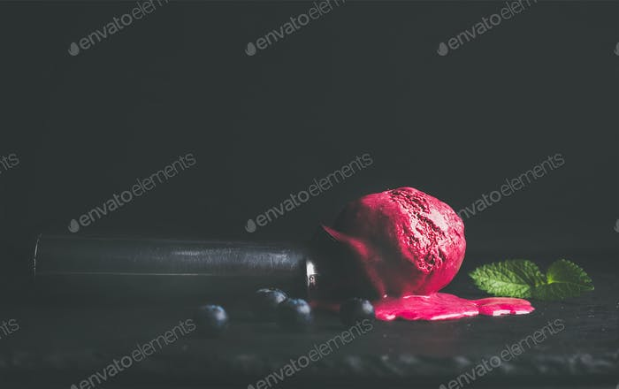 Melting blueberry ice-cream scoop over black background, copy space