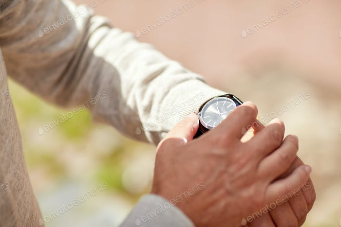 senior man checking time on wristwatch outdoors