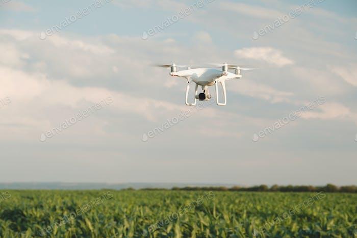 Weiße Drohne schwebt in einem leuchtend blauen Himmel