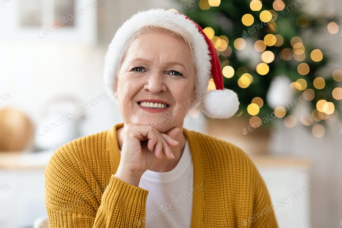 Portrait of cheerful old woman in Santa hat