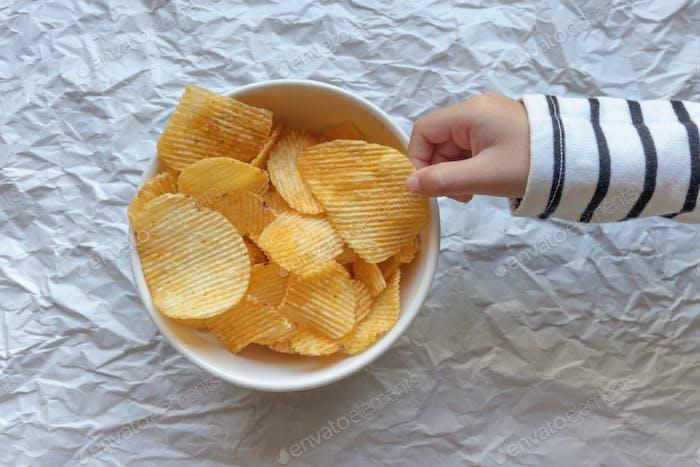 Hand des Mädchens holen einen Kartoffelchip in der weißen Schüssel