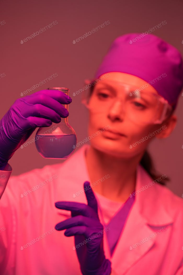 Gloved hands of young female pharmacist holding beak with liquid substance
