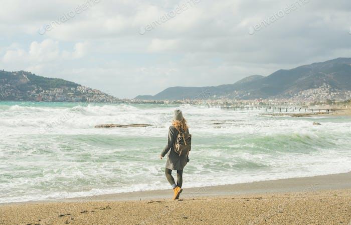 Young woman looking at stormy Mediterranean sea, Alanya, Turkey
