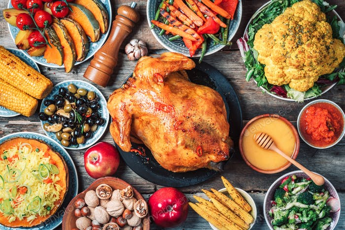 Roasted whole chicken, rice, pumpkin, corn, honey, nuts, vegetable salads over wooden background
