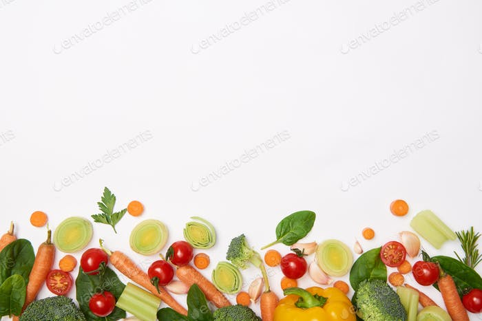 Top view of spinach leaves and vegetables on white background