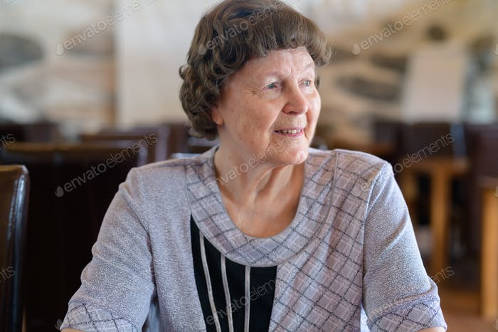 Happy Senior Woman Thinking At The Coffee Shop