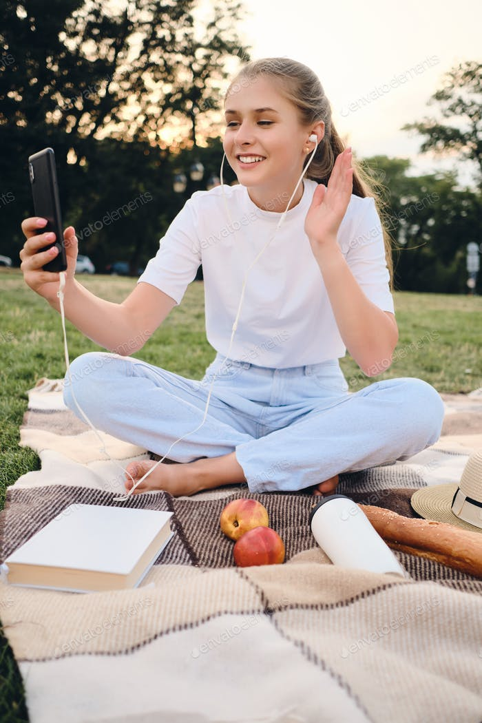 Pretty smiling teenage girl sitting on plaid happily talking on video chat on picnic in park