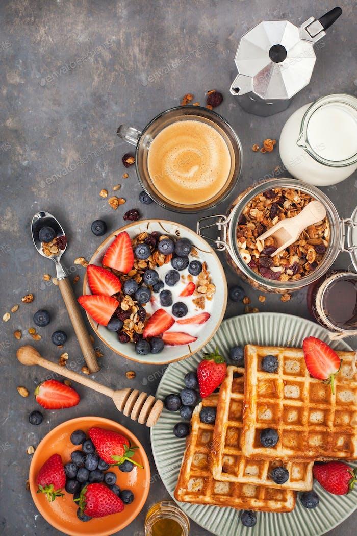 Frühstückstisch mit Müsli, Waffeln, Beeren und Kaffee