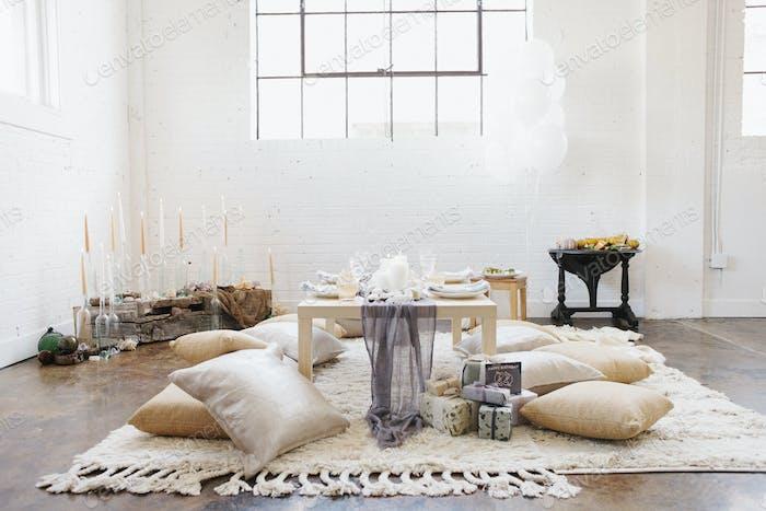 Eine Wohnung mit einem Tisch für eine Feier Mahlzeit. Kissen auf dem Boden.