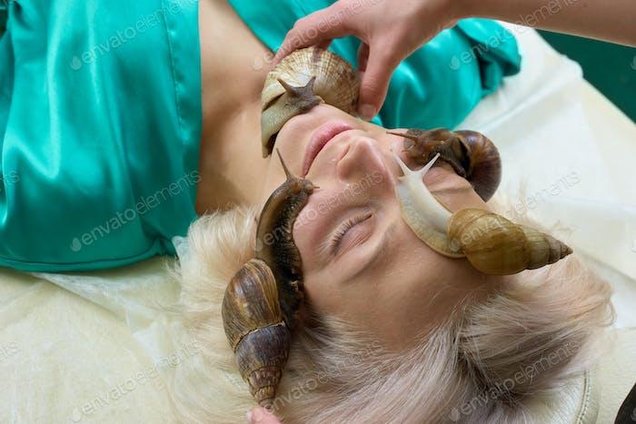 Caracoles en la cara femenina en el salón de spa