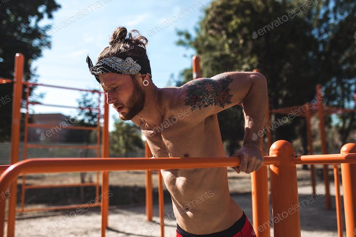 Young athletic man in headband with a naked torso with tattoos doing push-ups on the uneven bars