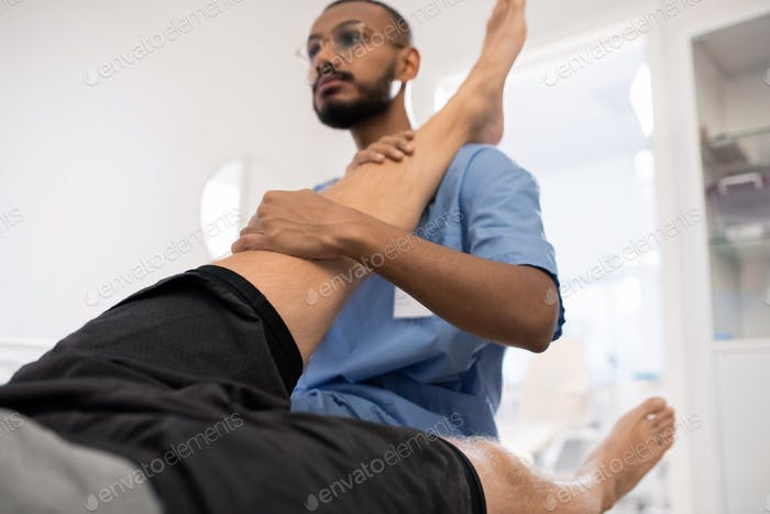 Qualified medical professional massaging sick knee of patient in hospital