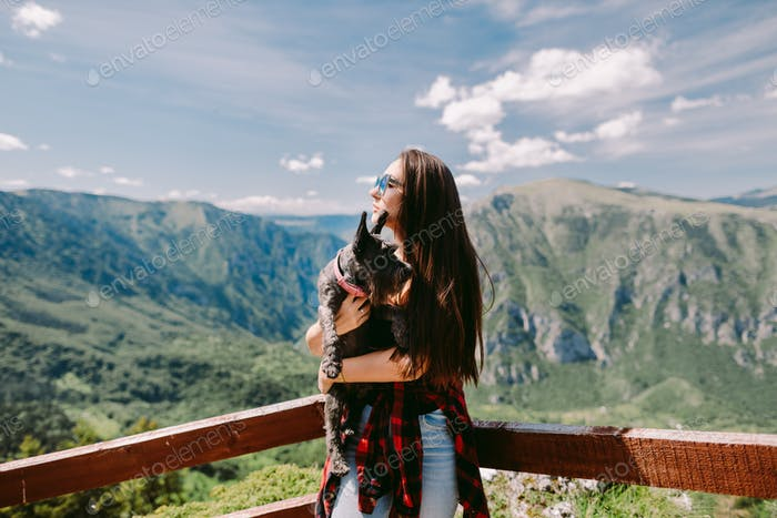 beautiful woman travel with cute dog in mountains